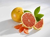 One whole and one half grapefruit with segments and wedge