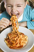 Small girl eating ribbon pasta with tomato sauce