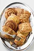 Assorted Danish pastries on silver platter with cake tongs