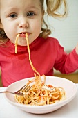 Small girl eating spaghetti