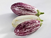 Two striped aubergines, one halved
