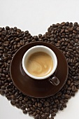 A cup of coffee on a heart of coffee beans