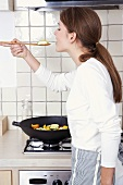 Woman tasting stir-fried vegetables cooked in wok