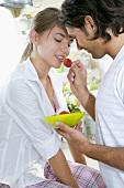 Man feeding woman a fresh strawberry