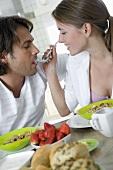 Woman feeding man a spoonful of muesli