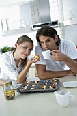 Young couple eating fresh fruit tarts and drinking coffee