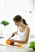 Young woman cutting up peppers