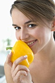 Young woman holding a yellow pepper up to her mouth