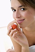 Young woman holding a strawberry with a yoghurt tip