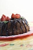 Gugelhupf with chocolate sauce and fresh strawberries