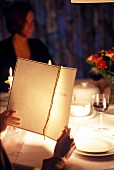 Guest reading menu in restaurant with woman in background