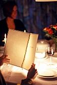 Gast liest Speisekarte im Restaurant mit Frau im Hintergrund