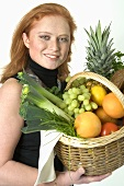 Young woman holding a basket of fruit and vegetables