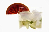 Mineral water with lime wedges, ice cubes and blood orange