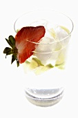Mineral water with lime wedges, ice cubes and strawberry