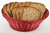 Mixed-grain bread, sliced, in red bread basket