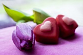 Two heart-shaped chocolates with purple tulip