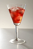 A glass of cranberry juice with ice cubes