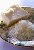 Parmesan am Stück und gerieben in einem Teller