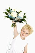 Blond boy holding bouquet of white roses