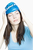 Young woman cooling her forehead with an ice pack