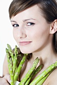 Young woman holding green asparagus