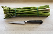 A bundle of green asparagus with knife