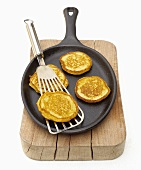 Small corn pancakes in frying pan on a wooden board