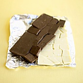 Two broken chocolate bars on aluminium foil