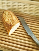 A piece of baguette with knife in a bread basket