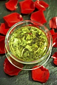 Green tea - infusion surrounded by red rose petals