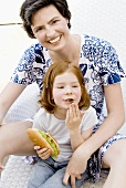 Woman sitting behind small girl with hot dog