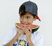 Boy biting into a slice of watermelon