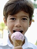 Junge isst eine Kugel Erdbeer-Vanille-Eis in der Waffel