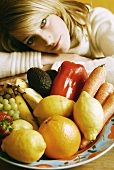 Young woman sitting in front of plate of fruit & vegetables