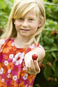 Blond girl holding a raspberry in her hand