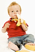 Small boy holding a banana in his hand