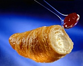 A croissant with a spoonful of raspberry jam