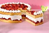 A strawberry cream cake with a piece cut