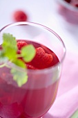 A glass of raspberry juice with fresh raspberries