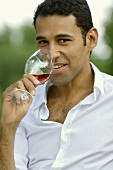 Young man drinking a glass of rosé wine