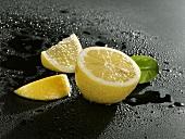 Half a lemon and two lemon wedges
