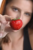Young woman holding a strawberry