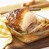 Roast pork with crackling on bed of vegetables
