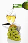 Ein Glas Weisswein eingiessen