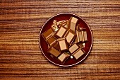 Pieces of chocolate on brown plate
