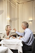 Man feeding woman dessert in a restaurant