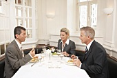 A woman and two men at a business meal