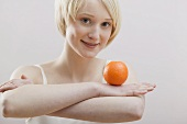Young woman balancing an orange on folded arms