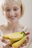 Young woman holding bananas